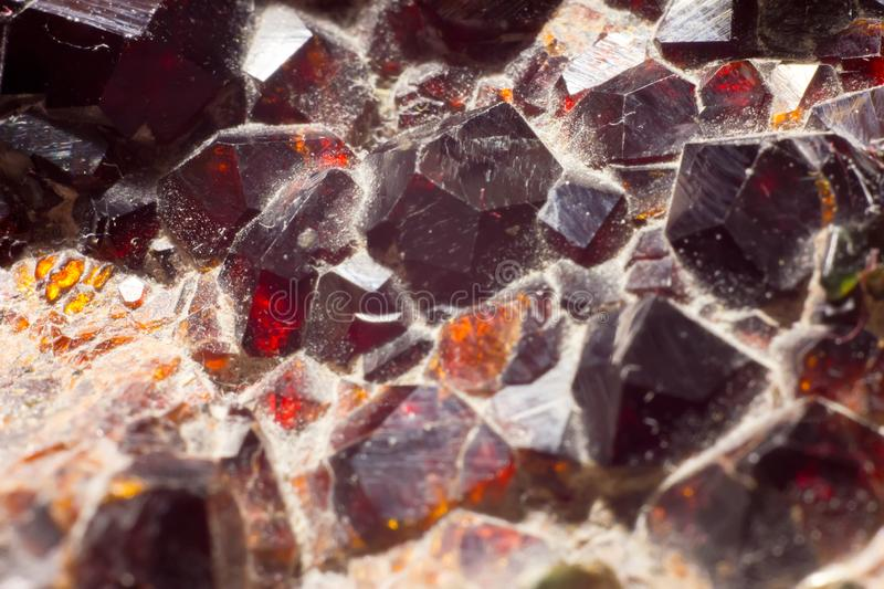 Unprocessed garnet. Macrophoto of druza unprocessed garnet. Pure colors this mineral glow in bright light. Beautiful color of wine and honey make this cristals stock photography