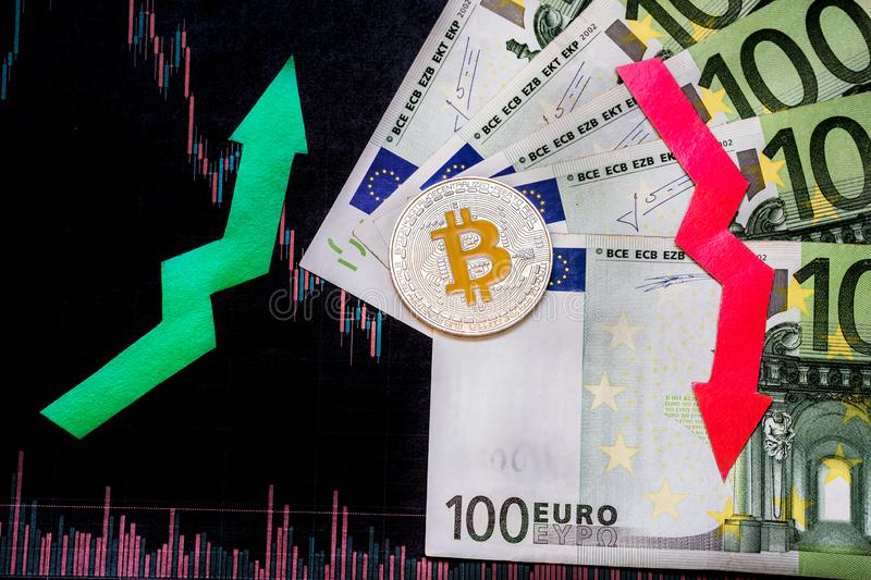 Unprofitable investment of depreciation of virtual money bitcoin. Red and green arrow, silver bitcoin and euro go down on paper stock photo