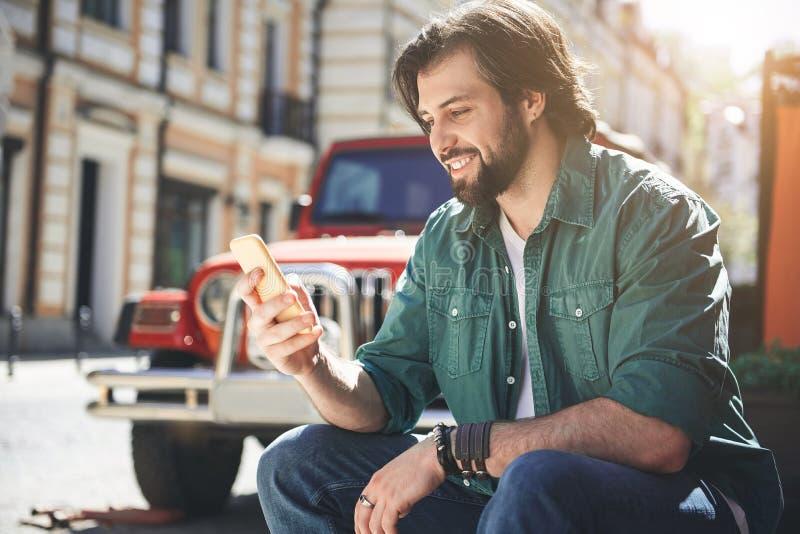 Unrasierte männliche Person, die draußen Smartphone verwendet stockbilder