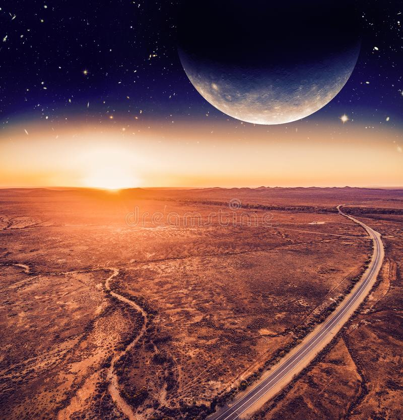 Unreal landscape - dark planet over road. Unreal landscape - dark planet over road winding through desert landscape at sunset. Elements of this image are royalty free illustration