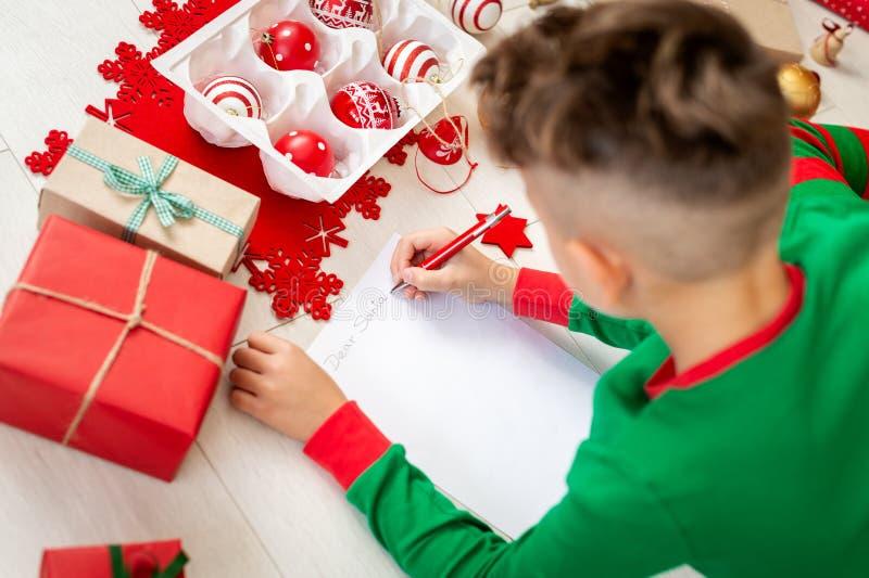 Unrecognisable chłopiec jest ubranym boże narodzenie piżamy pisze liście Santa na pokój dzienny podłodze Chłopiec pisze jego boże fotografia royalty free