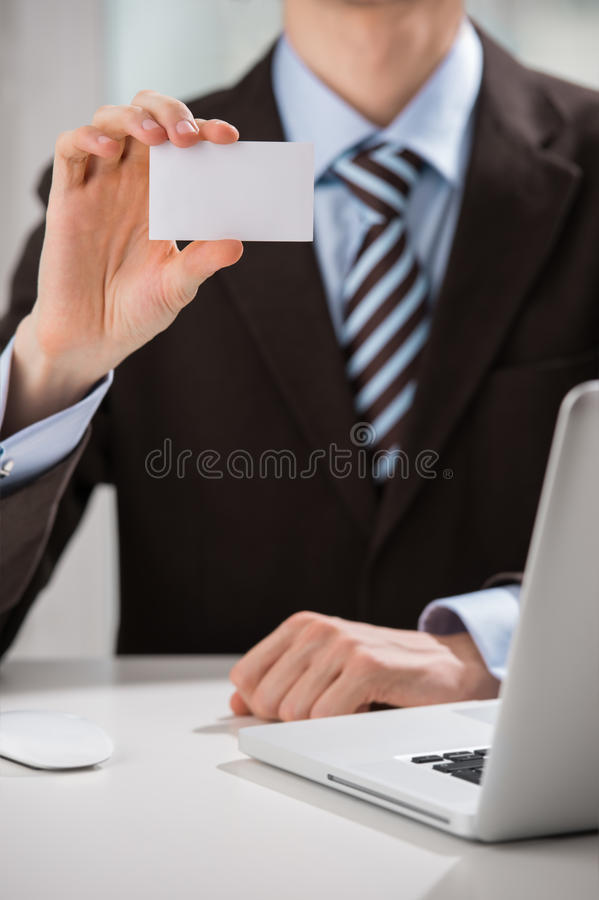 Unrecognisable confident business man wearing suit. Closeup of torso of confident business man wearing elegant suit sharing his blank business card at his royalty free stock photo