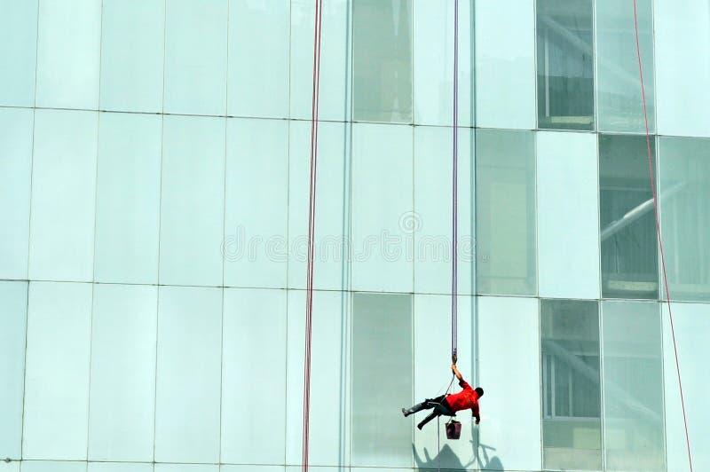 Unrecognisable fönsterrengöringsmedel som gör ren en kontorsbyggnad royaltyfria foton