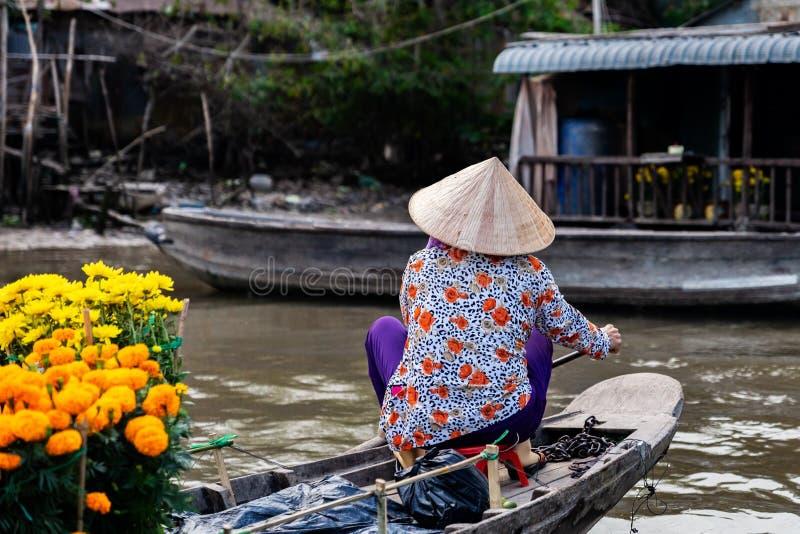 Unrecognisable Frau, die den traditionellen vietnamesischen Hut, voll rudernd auf einem Boot von Blumen, um Tet vorzubereiten, de stockbild