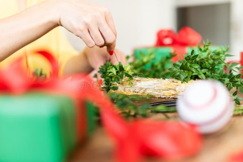 Unrecognisable Frau, die Weihnachtskranz im Wohnzimmer macht DIY-Weihnachtsdekorationskonzept Hände schließen oben stockfotos