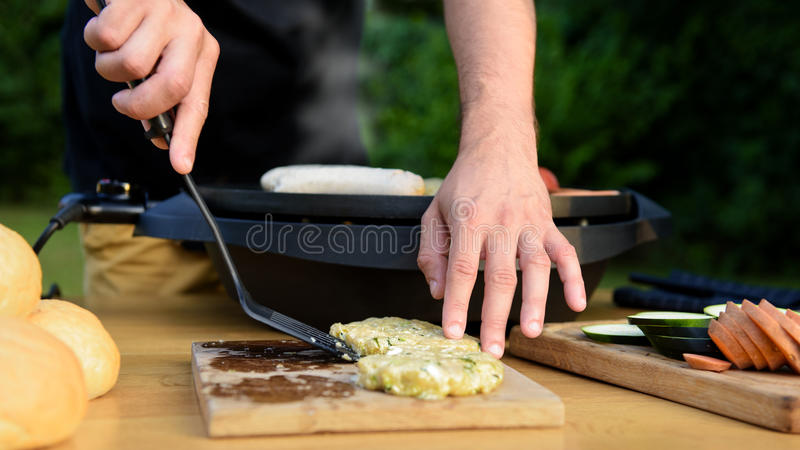Unrecognisable man using electric grill. Garden grill party, summer barbecue royalty free stock photos