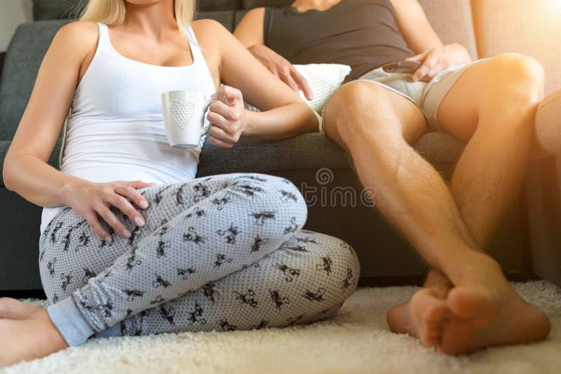unrecognisable para relaksuje w domu, oglądający telewizję, pije kawę zdjęcia royalty free