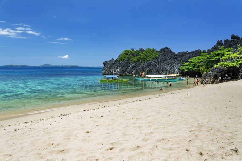 Unrecognisable people playing by the Banca boats on Lahus Island beach, Caramoan, Camarines Sur Province, Luzon in the Philippines. Unrecognisable people playing stock photo
