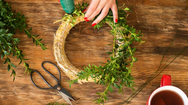 Unrecognisable woman making christmas wreath in living room. DIY Christmas decoration concept. Hands close up. stock photography