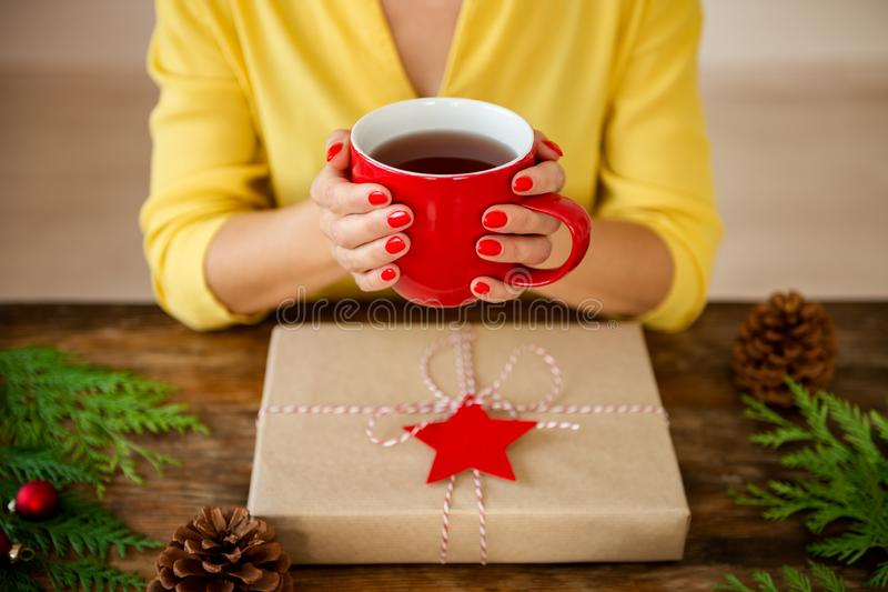 Unrecognisable woman sitting at a table with beautifully wrapped christmas present, holding cup of tea. Gift wrapping concept. royalty free stock photos