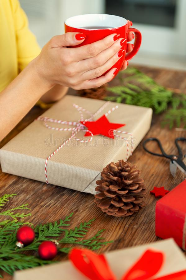 Unrecognisable woman sitting at a table with beautifully wrapped christmas present, holding cup of tea. Gift wrapping. stock images