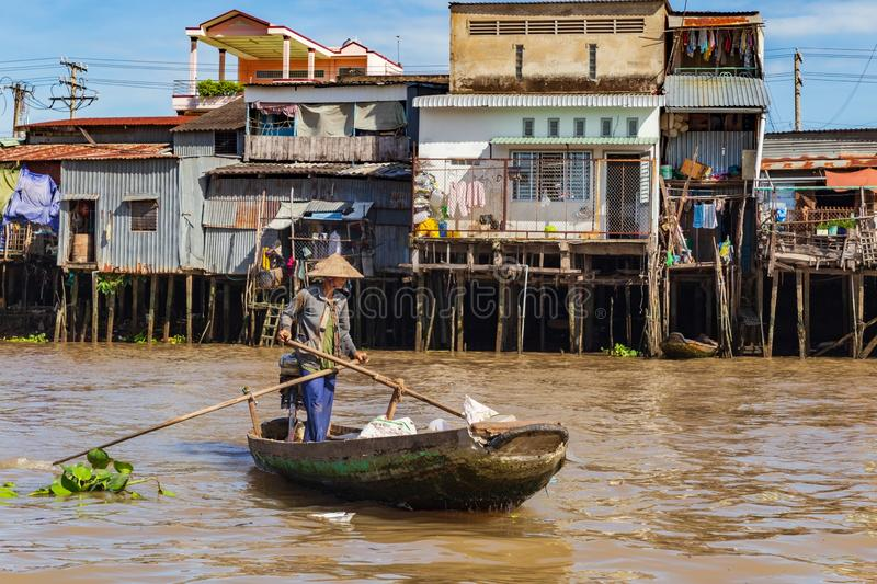 Unrecognisable woman wearing traditional Vietnamese conical hat rowing on a boat by the houses of Can Tho, Mekong Delta, Vietnam. Unrecognisable woman wearing royalty free stock image