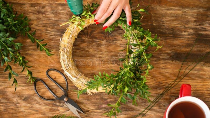 Unrecognisablevrouw die Kerstmiskroon in woonkamer maken DIY-het concept van de Kerstmisdecoratie De handen sluiten omhoog stock fotografie