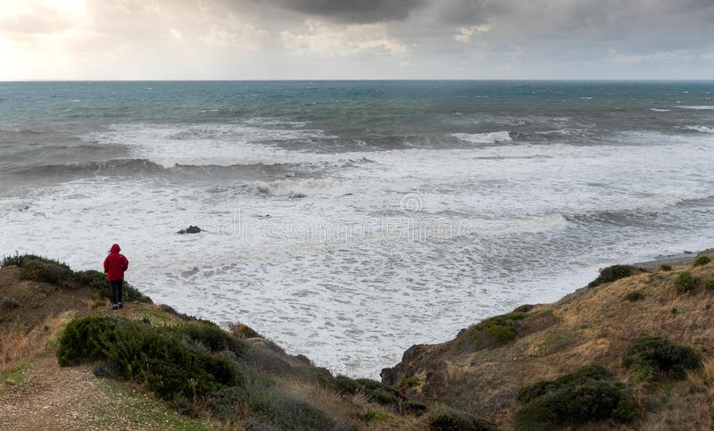 Unrecognised person standing the edge of a cliff end enjoying the dramatic stormy sea and sky stock image