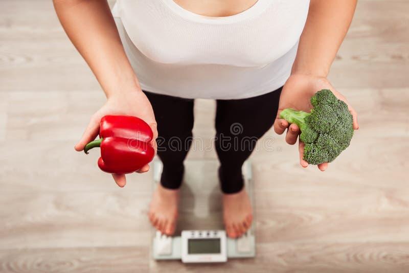 Unrecognizable λεπτή γυναίκα που ελέγχει το βάρος στην κλίμακα και που κρατά τα λαχανικά στοκ εικόνα