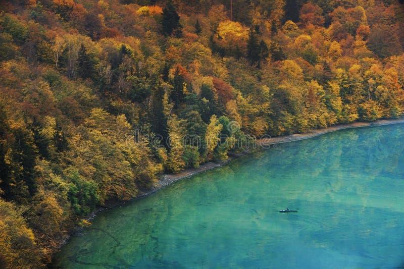 Unrecognizable ψαράς σε μια βάρκα σε μια λίμνη και το φθινοπωρινό δάσος σε μια τράπεζα Φωτογραφία με τα πολύ τονισμένα χρώματα στοκ εικόνες