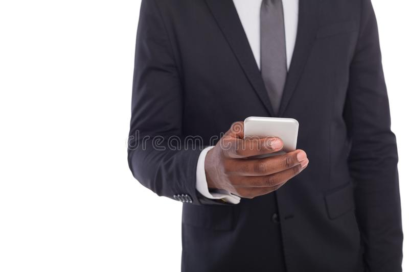 Unrecognizable businessman in suit with smartphone. Unrecognizable african american businessman in suit with smartphone, copy space. Black man using mobile phone stock image