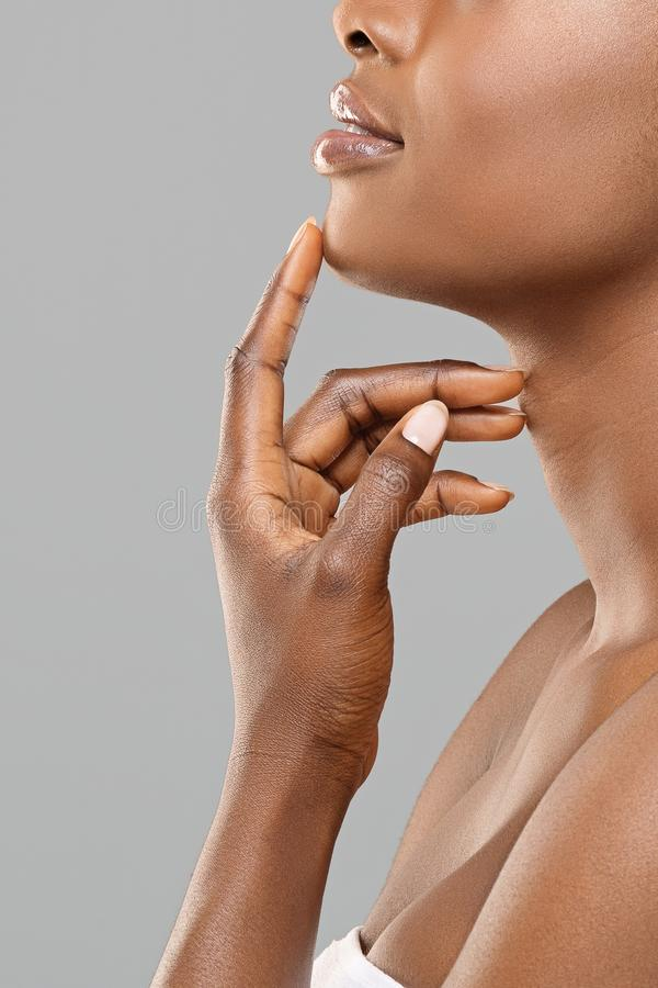 Unrecognizable afro woman touching her chin after plastic surgery. Chin augmentation. Unrecognizable afro woman touching implant in her face, happy with result stock photos