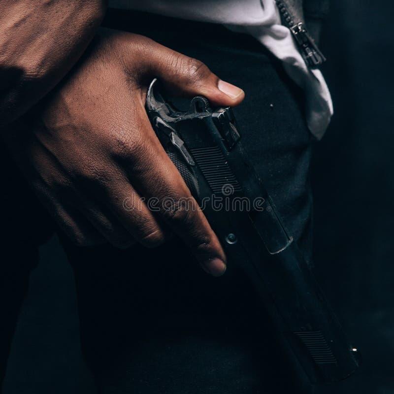 Unrecognizable armed black criminal man closeup royalty free stock image