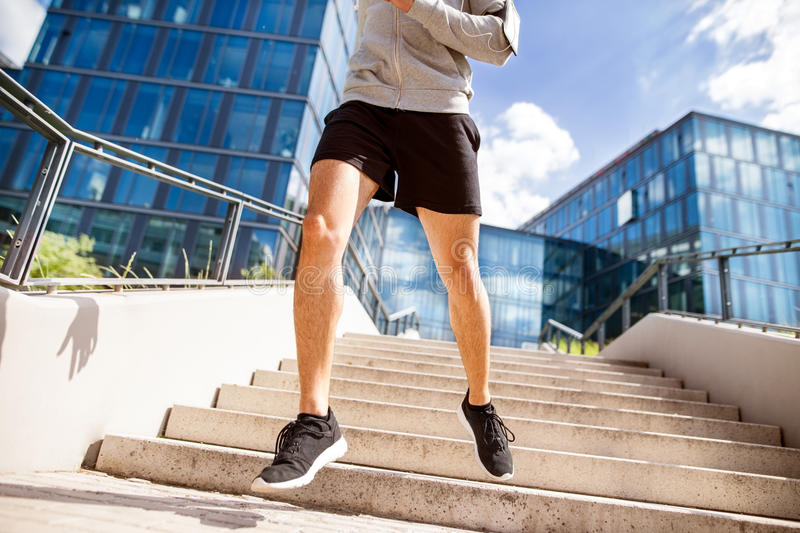 Unrecognizable athlete running in front of glass buildings. royalty free stock photography
