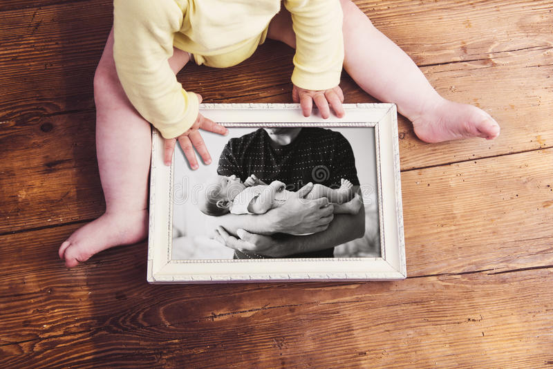 Unrecognizable baby holding picture frame. Fathers day. royalty free stock photo