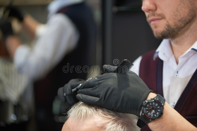 Unrecognizable barber cutting hair of his client in barbershop royalty free stock image