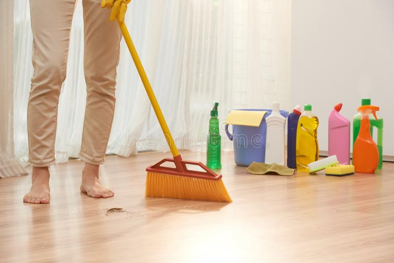 Sweeping Floor with Broom. Unrecognizable barefoot woman sweeping floor with broom while wrapped up in housecleaning, detergent bottles, sponges and rags located royalty free stock photo