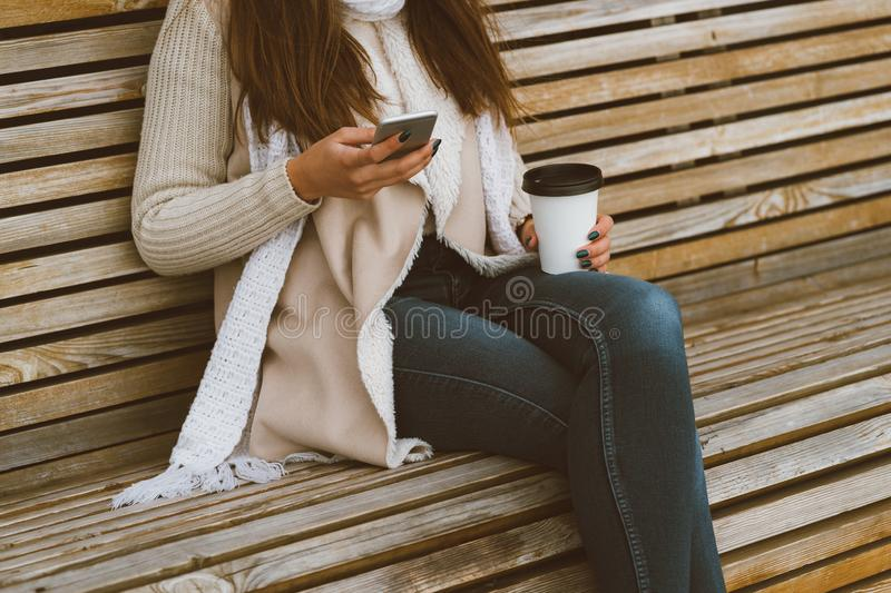 Unrecognizable beautiful young girl drinking coffee, tea from plastic mug in autumn, winter and talking on mobile phone. Woman stock images