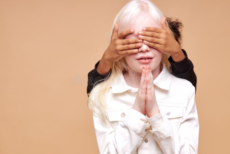 Unrecognizable black boy close albino girls eyes from back. Unidentified black boy close albino girls eyes from back. friendly diverse kids isolated in studio royalty free stock photos