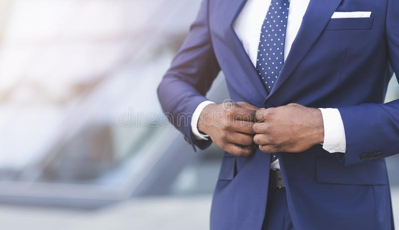 Unrecognizable Black Businessman Fastening Jacket In Urban Area. Business Attire. Unrecognizable Black Businessman Fastening Suit Jacket Standing In Urban Area royalty free stock photos