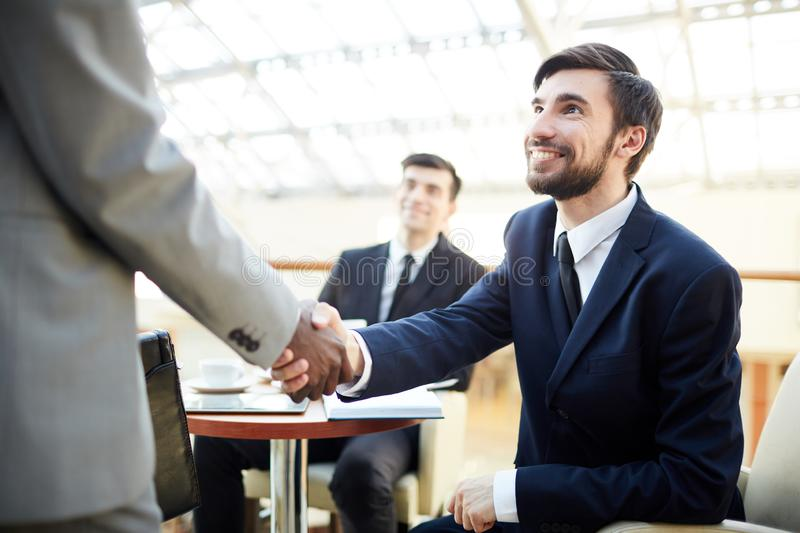 Congratulating business partners with successful deal. Unrecognizable black businessman in suit congratulating business partners with successful deal after stock photos