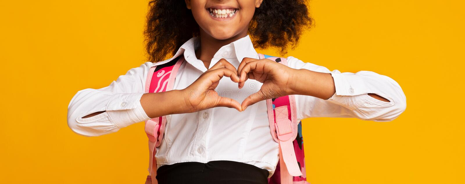 Unrecognizable Black Schoolgirl Showing Heart Shape Gesture On Yellow Background. Love School. Black Elementary Schoolgirl Showing Heart Shape Gesture With royalty free stock photos
