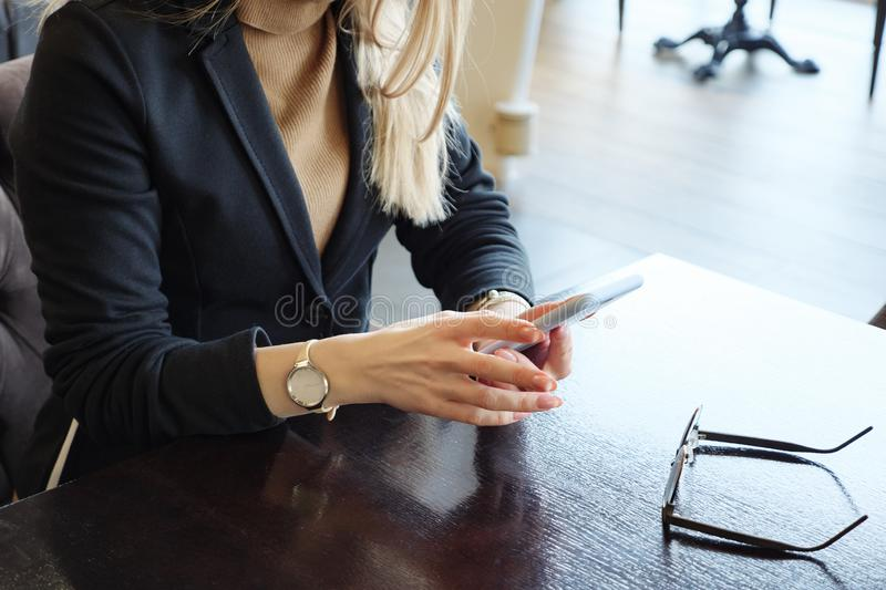 Unrecognizable blonde business woman in suit with phone sitting at a table in a cafe royalty free stock images
