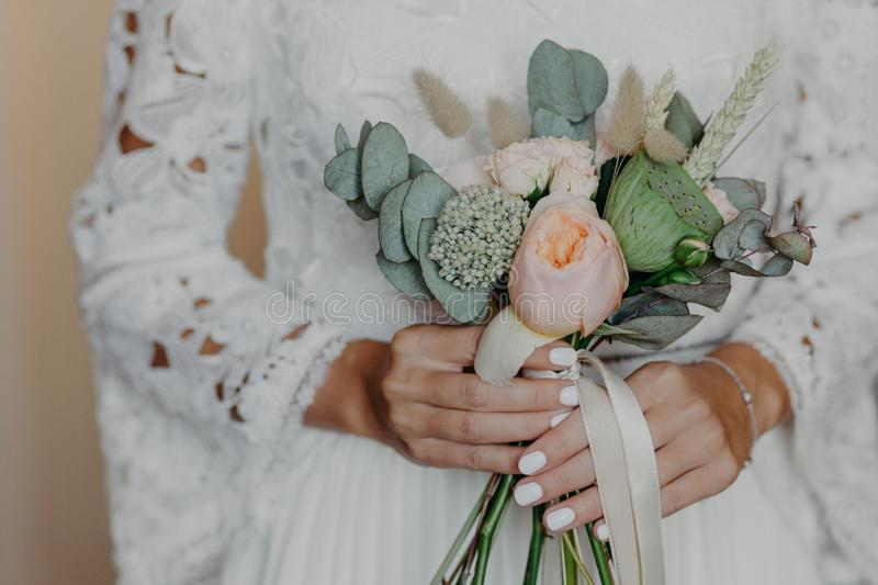 Unrecognizable Bride with tender manicure, holds beautiful bouquet, wears white wedding dress. Special occasion, ceremony concept royalty free stock photography