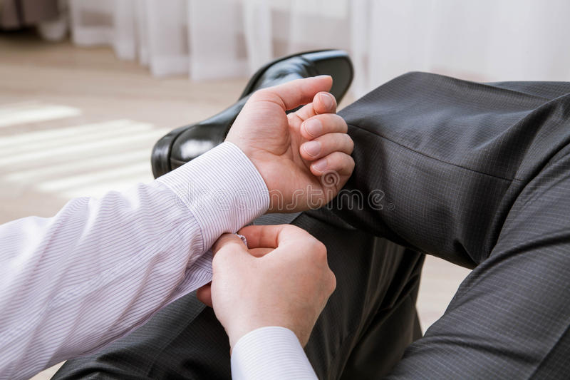 Unrecognizable businessman clasping a cuff. Indoors royalty free stock photography