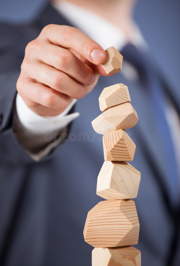 Unrecognizable businessman forming a wooden pyramid. Closeup shot stock image
