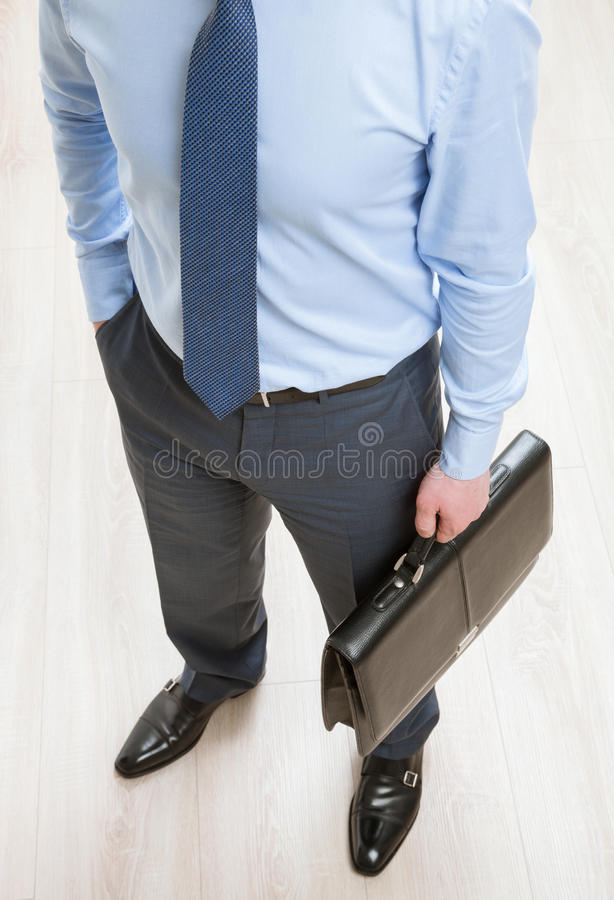 Unrecognizable businessman holding a black briefcase. View from above stock photography
