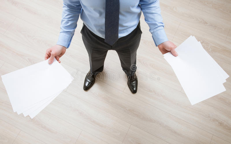 Unrecognizable businessman. Holding empty sheets of paper, view from above stock photography