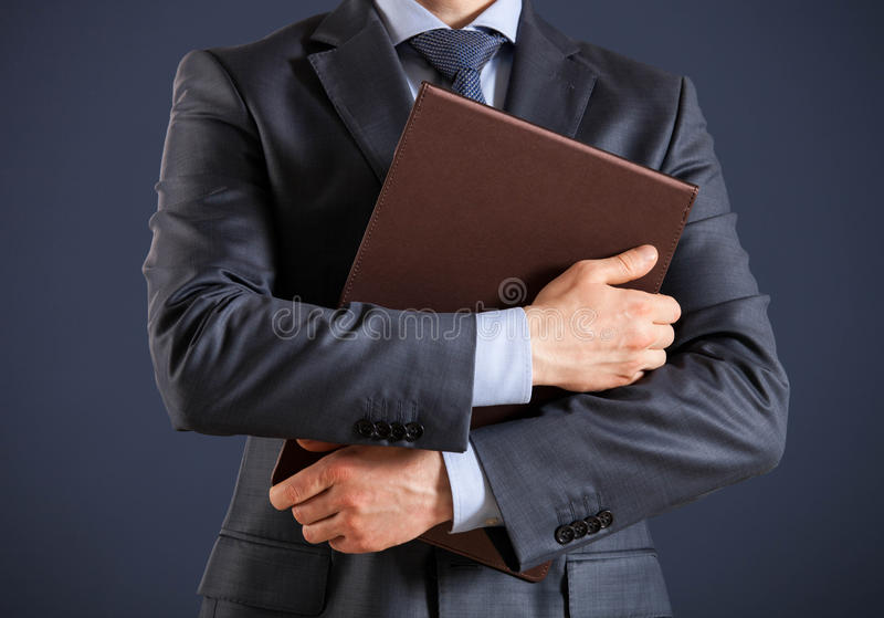 Unrecognizable businessman holding folders with documents. Dark background stock image