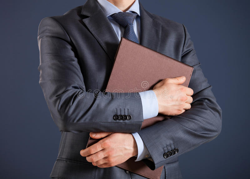 Unrecognizable businessman holding folders with documents. Dark background stock photos