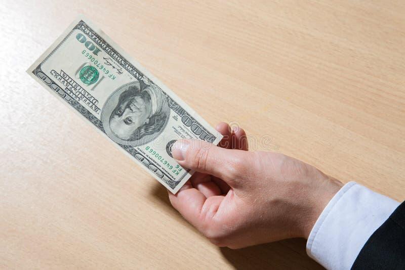 Unrecognizable businessman holding paper money/dollars. Closeup shot stock photography