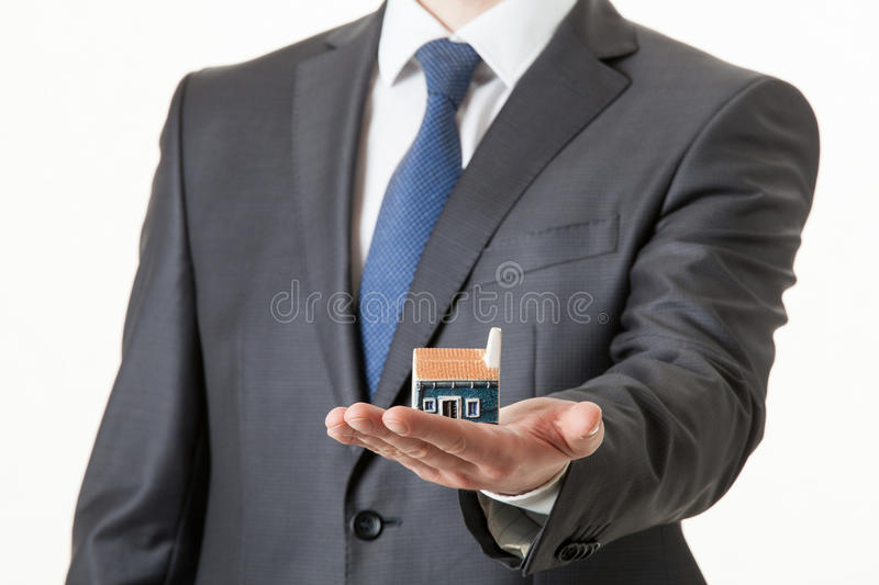 Unrecognizable businessman holding a toy house. On his palm stock photos