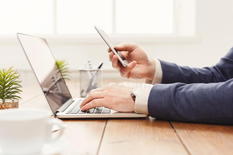 Unrecognizable businessman using laptop and phone. Unrecognizable businessman with mobile app and laptop in modern office, working on computer and smartphone royalty free stock photography