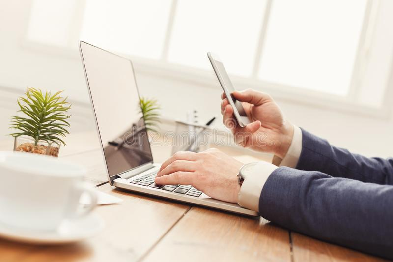 Unrecognizable businessman using laptop and phone. Unrecognizable businessman with mobile app and laptop in modern office, working on computer and smartphone royalty free stock image