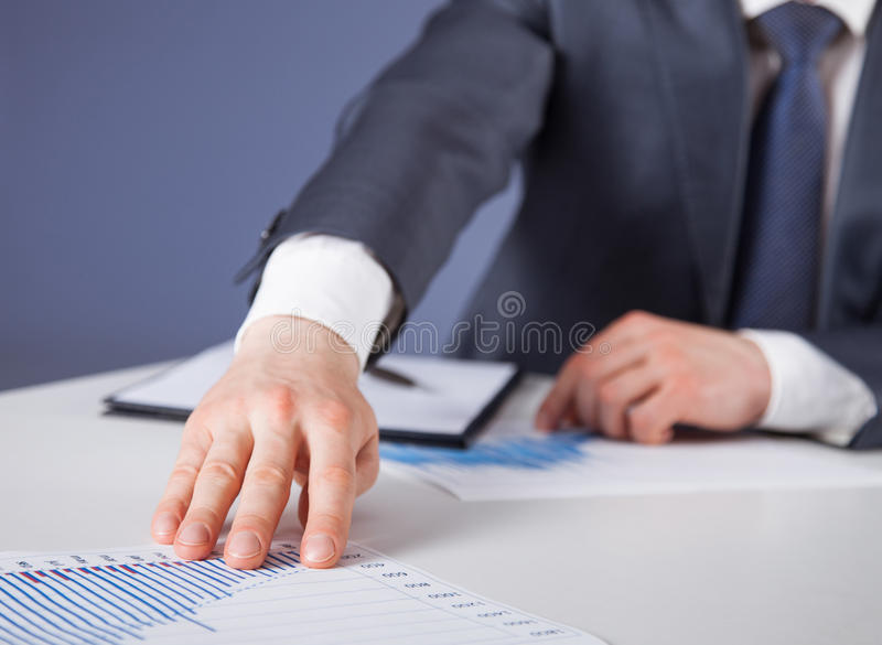 Unrecognizable businessman proposing to examine a new project. Blue background royalty free stock photos