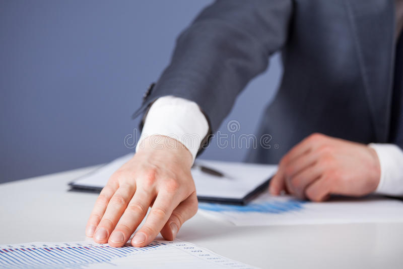 Unrecognizable businessman proposing to examine a new project. Blue background royalty free stock photo
