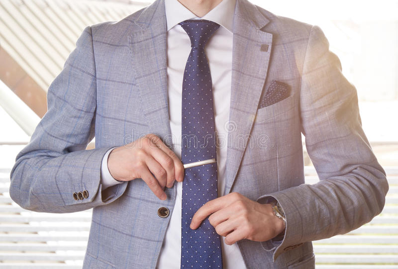 Unrecognizable businessman setting the tie straight by adjusting his tie pin. Backlighting with a lens flare effect. stock image