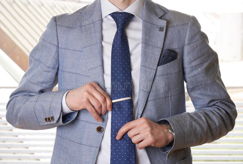 Unrecognizable businessman setting the tie straight. Simple and clean royalty free stock photography