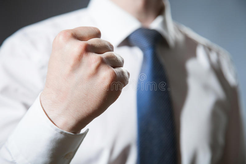 Unrecognizable businessman showing a strong fist. Dark background royalty free stock photos