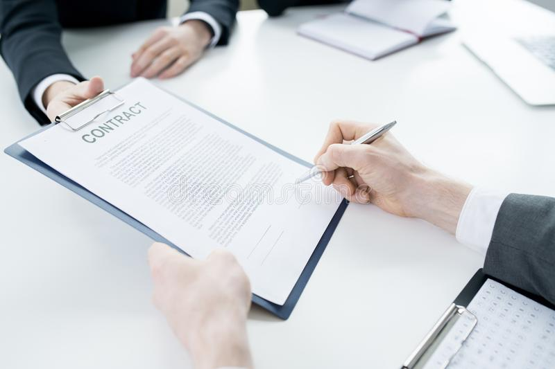 Unrecognizable Businessman Signing Contract. Close up of unrecognizable businessman signing contract during meeting with partners at table in conference room stock photography